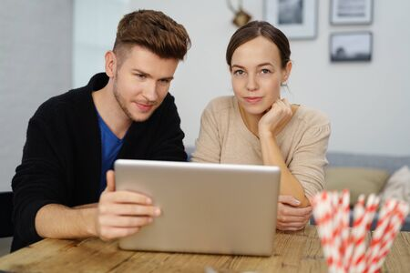 couple home: young man and woman sitting at desk at home with woman looking at camera, hand on chin