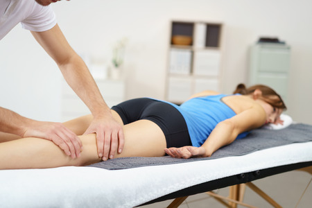 massaggio: Massaggiatore Massaggiare le gambe di una donna sdraiata prona sul letto. Archivio Fotografico