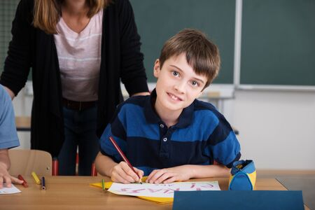 child boy: Cute Young School Boy Smiling at the Camera While Working at his Table Inside the Classroom.