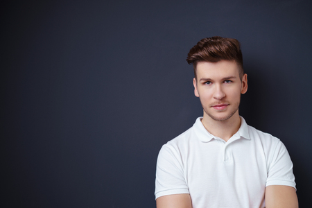 deadpan: Handsome young man with a serious thoughtful expression standing against a dark grey background with copyspace, head and shoulders portrait Stock Photo