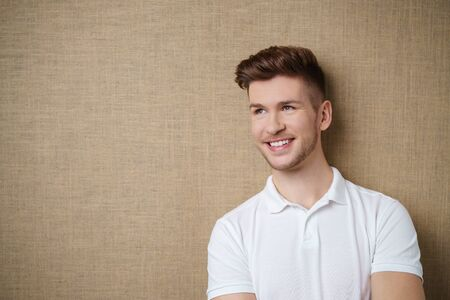 man looking: trendy young man smiling and looking away against a light brown background