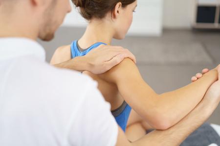 física: Hombre del terapeuta físico masajear el brazo dañado y hombro de una mujer joven lentamente.