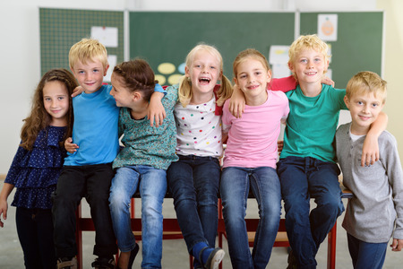 school classroom: Cute Kids Holding Each Others Shoulders with Happy Facial Expressions Inside the Classroom