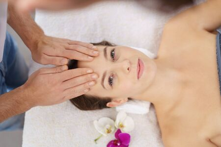 High Angle View of a Young Young Woman Looking at the Camera while Enjoying a Face Massage at the Spa.