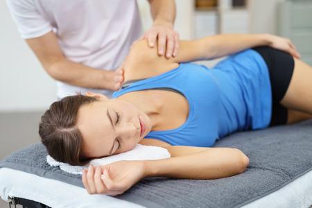 epaule douleur: Jeune femme couchée dans le lit Alors que son physiothérapeute est donner un massage à son épaule blessée. Banque d'images