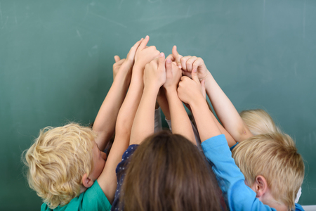 Kids Raising their Arms at the Center together and Showing Thumbs Up Hand Signs Against Green Chalkboard.