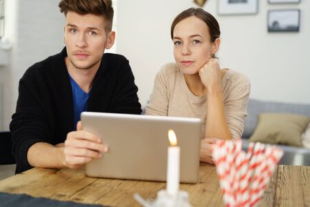 unemotional: young couple sitting at desk with notebook and a thoughtful expression