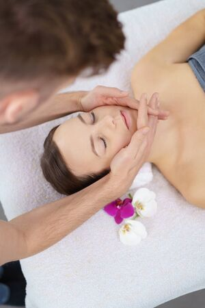 spa flower: High Angle View of a Young Woman Lying on Bed and Enjoying a Head Massage in the Spa. Stock Photo