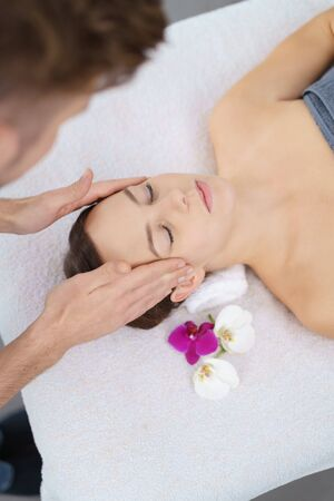 high angle view: High Angle View of a Young Woman Lying on Bed and Enjoying a Head Massage in the Spa. Stock Photo