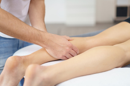manipulating: Close up Male Physical Therapist Massaging the Leg of a Patient Who is Lying on Therapy Bed. Stock Photo