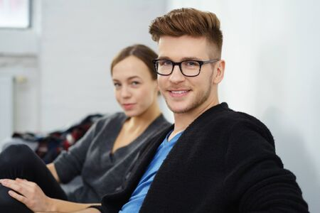 hair man: portrait of a trendy young man with glasses and his girlfriend in background at home