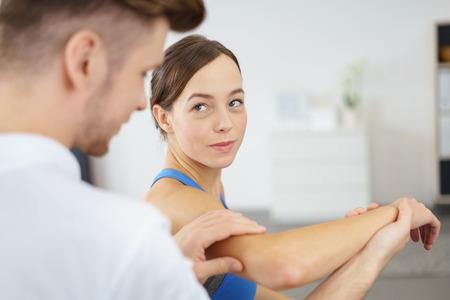codo: Mujer joven que admira su terapeuta físico masculino mientras trabajaba en su brazo dañado.