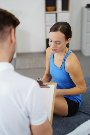 physical therapist: physiotherapist talking to a young female patient in a physio room. Stock Photo