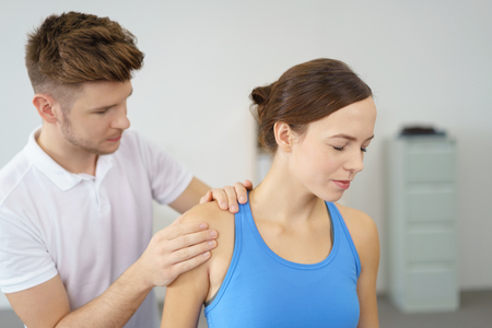 enduring: Young Woman Closing her Eyes While Enduring the Pain of a Shoulder Massage Given by her Physical Therapist. Stock Photo