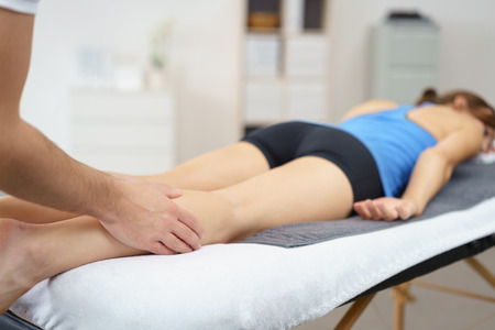 hamstring: Professional Physical Therapist Massaging the Injured Legs of a Female Patient Lying Prone on a Therapy Bed. Stock Photo