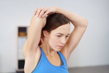 concentrates: Close up Serious Woman Stretching her Injured Arm Slowly at the Back of her Head.