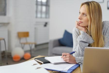 escribiendo: Mujer con la computadora portátil y el papeleo que hace algunas notas en su tabla en el país