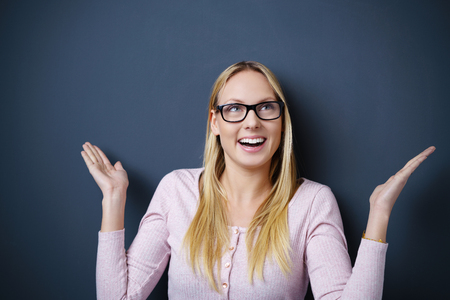 befuddled: blond woman making a surprised gesture with her arms Stock Photo