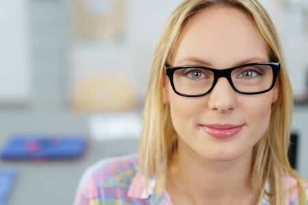 women face stare: Head and Shoulder Shot of a Young Businesswoman Wearing Eyeglasses, Smiling at the Camera Against Blurred Office. Stock Photo