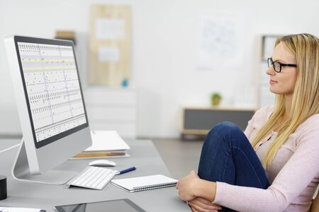 specs: modern young woman inside the workplace looking at a chart on the monitor with arms around her knee