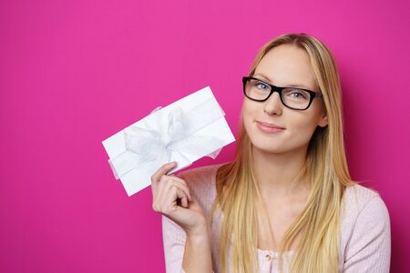 Attractive young blond woman displaying a decorative envelope or letter tied with a bow to the camera with a pleased smile over a bright pink background with copy space Stockfoto