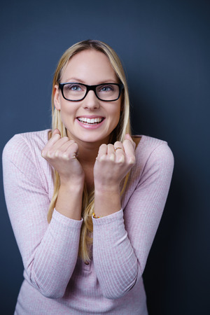 exuberant: Half Body Shot of an Excited Young Woman Looking Away Against Gray Wall Background. Stock Photo