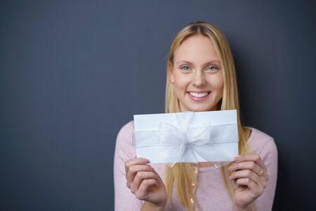 Hübsche junge Frau, die weißes Geschenk anhält, lächelt in der Kamera gegen dunkelgraue Wand mit Textfreiraum auf der linken Seite.
