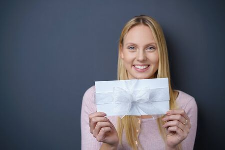 exultant: Pretty Young Woman Holding White Gift, Smiling at the Camera Against Dark Gray Wall with Copy Space on the Left Side. Stock Photo