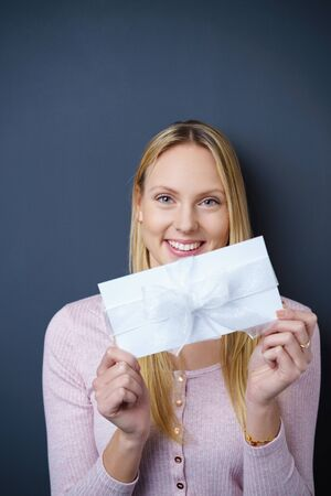 elated: Elated young woman showing a gift envelope decorated with a white ribbon and bow to the camera with a happy excited smile, over a blue background