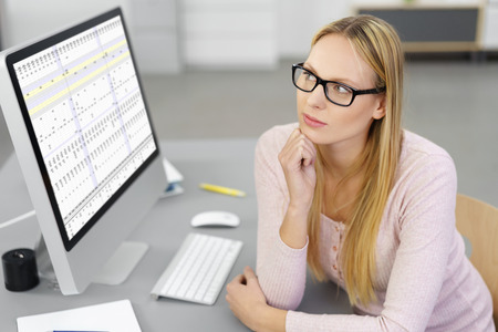 personal data assistant: Concerned businesswoman trying to solve a problem sitting at her desk at the office in front of a large desktop monitor staring thoughtfully into the distance with a solemn expression