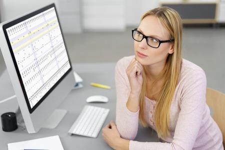 datos personales: Preocupados empresaria tratando de resolver un problema que se sienta en su escritorio en la oficina delante de un monitor de escritorio grande mirando cuidadosamente en la distancia con una expresión solemne