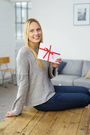 elated: Smiling elated young blond woman relaxing at home on her dining table displaying an envelope tied with a festive red ribbon and bow, conceptual of love or an award or prize