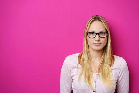 Head and shoulders portrait of a serious earnest young blond woman in glasses looking directly at the camera over a bright pink background with copy-space