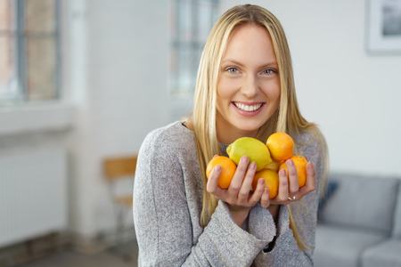 Healthy young woman holding assorted fresh citrus fruit as she smiles happily at the camera while standing in her living room at home in a healthy lifestyle and diet concept