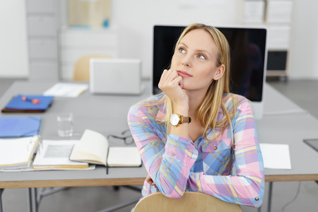 meditative: young businesswoman sitting at desk in the office looking up with a thoughtful facial expression
