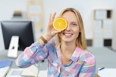 Playful young woman holding a sliced fresh juicy orange to her one eye with a big mischievous grin as she takes a break from work in the office Stock Photo