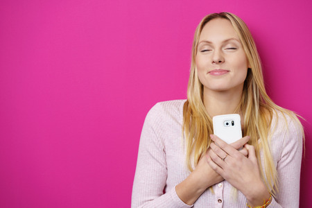 woman chest: Dreamy romantic young woman holding a mobile phone clasped to her chest and heart with a lovely smile of pleasure and her eyes closed in bliss, over a bright pink or magenta background with copy-space Stock Photo