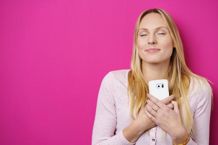 Zasněný romantický mladá žena držení mobilního telefonu sepjaté na hrudi a srdce s krásným úsměvem potěšení a zavřenýma očima v blaženosti, přes světlé růžové nebo purpurové pozadí s kopií vesmíru