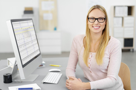 Smiling confident businesswoman wearing glasses sitting at her desk in her office in front of a desktop computer monitor with a spreadsheet visible, turning to give the camera a warm friendly smile