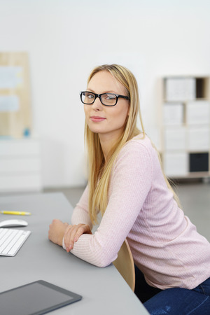 speculative: young woman sitting at desk in the office looking at camera with a smile
