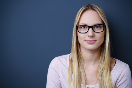 inscrutable: Close up Pretty Blond Woman Wearing Eyeglasses, Looking at the Camera Against Gray Wall with Copy Space on the Left Side. Stock Photo