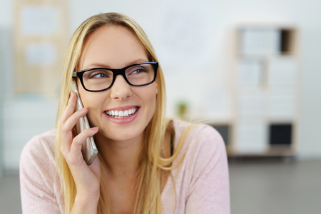 hablando por telefono: close up Happy Young Woman Talking to Someone Through Mobile Phone Against Blurred Office.