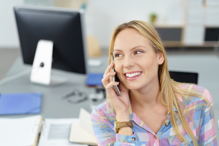 hablando por telefono: Mujer Bonita Oficina de hablar con alguien a través del teléfono móvil mientras se mira lejos con la expresión facial feliz.