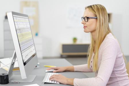 junge, blonde Geschäftsfrau auf Computer im Inneren des arbeitsplatz Standard-Bild