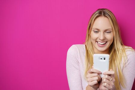 spontaneous expression: Happy blond woman looking at her mobile phone with a surprised smile against a pink background in studio