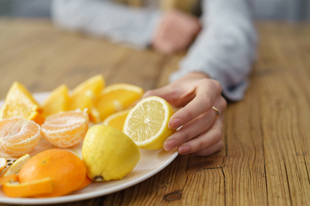 citrus: Woman Hand Putting Fresh Healthy Lemon and Orange Fruit on Plate, Placed on top of a Wooden Table. Stock Photo