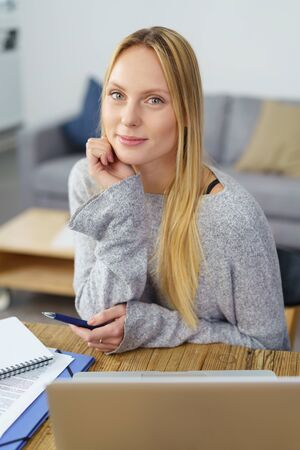hand on the chin: young woman at her table at home with laptop and paperwork, leaning chin on hand