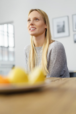 Low angle view across a dining table with fruit of an attractive woman sitting listening or daydreaming looking up into the air with a lovely smile