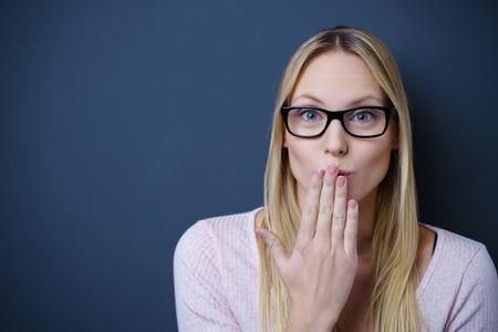 Close up abbastanza giovane donna che indossa occhiali da vista, Visualizzazione Ops Espressione alla macchina fotografica contro muro grigio con spazio di copia.