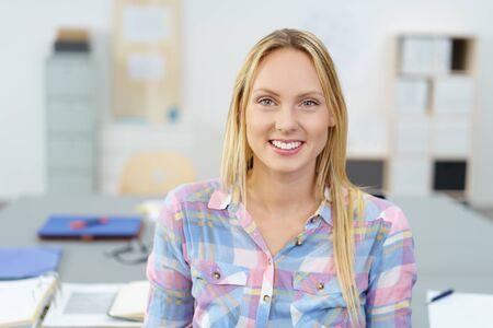 caras felices: Close Up Mujer de Oficina bastante joven sonriendo a la cámara mientras estaba sentado en su escritorio. Foto de archivo
